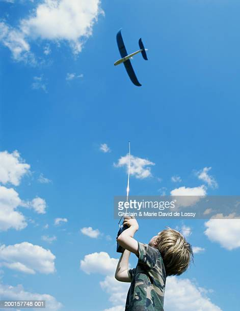 Boy (3-5) playing with remote control plane, low angle view