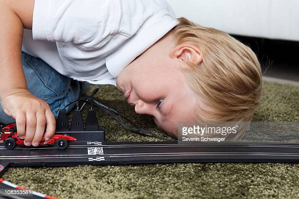 Boy playing with slot race track