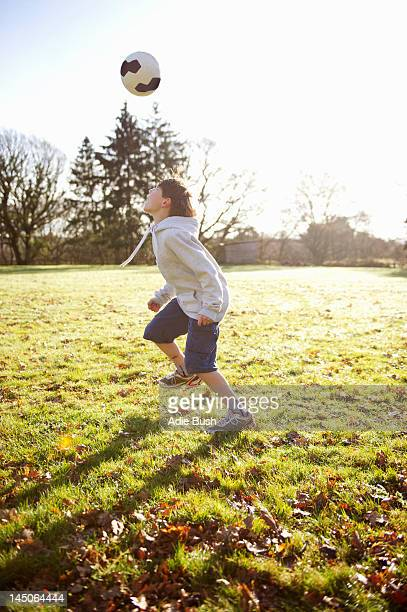 Boy playing with soccer ball in meadow
