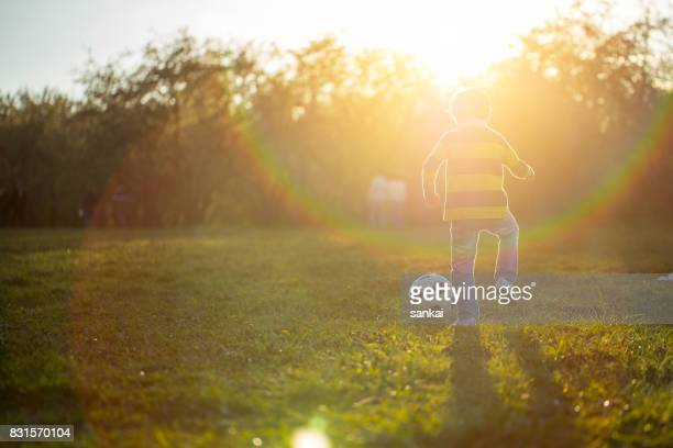 Boy playing with soccer ball in public park at sunset