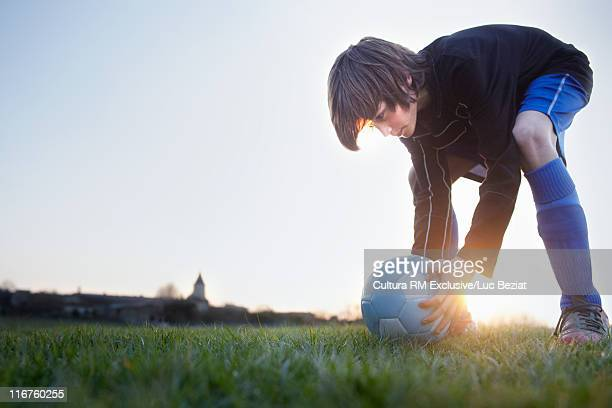 Boy playing with soccer ball outdoors