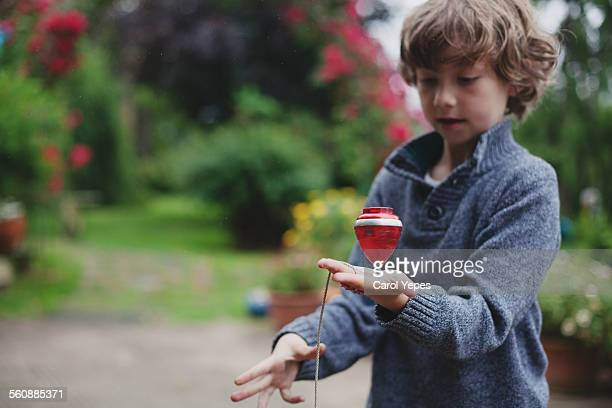 Boy playing with spinning top