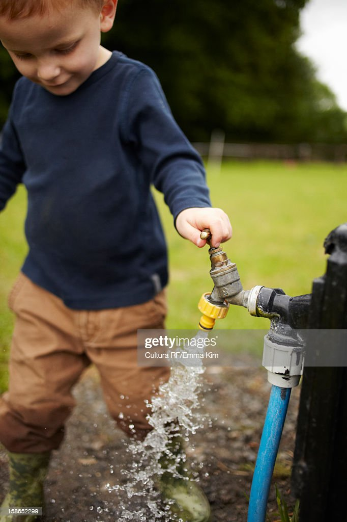 Boy playing with spout outdoors : Stock Photo