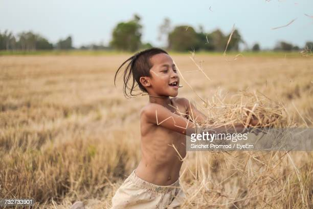 Boy Playing With Straws While Standing On Field At Farm Against Sky