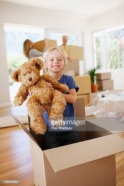 Boy playing with teddy bear in box in new house