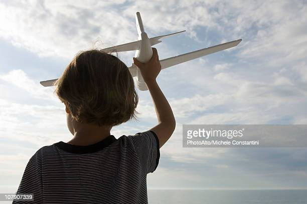 Boy playing with toy airplane, rear view
