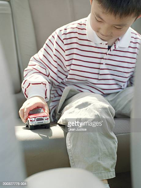 Boy (4-6) playing with toy car in van