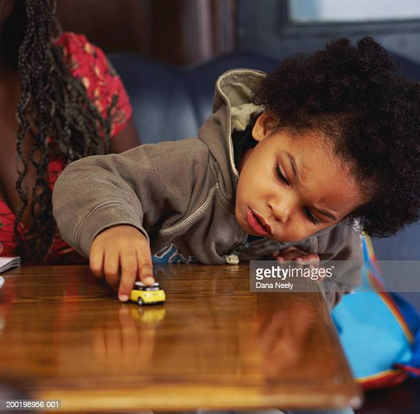 Boy (2-4) playing with toy car on table by mother