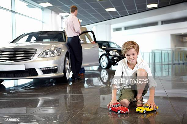 Boy playing with toy cars in automobile showroom