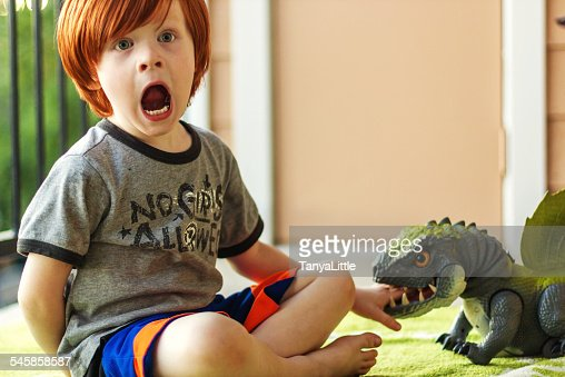 Young boy (4-5) playing with toy dinosaur