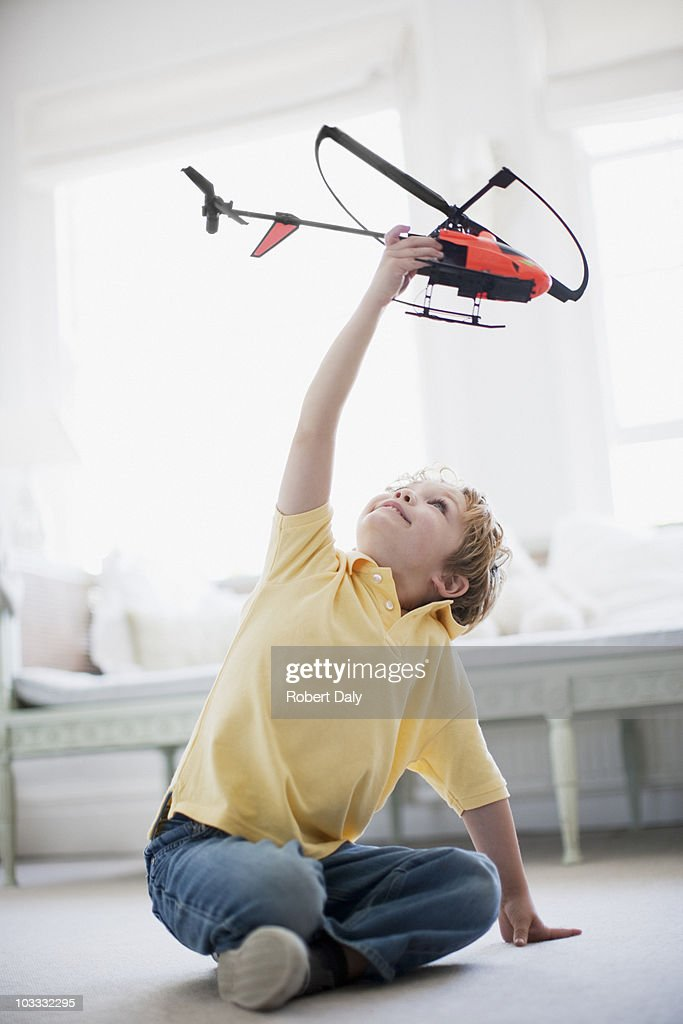 Boy playing with toy helicopter : Stock Photo
