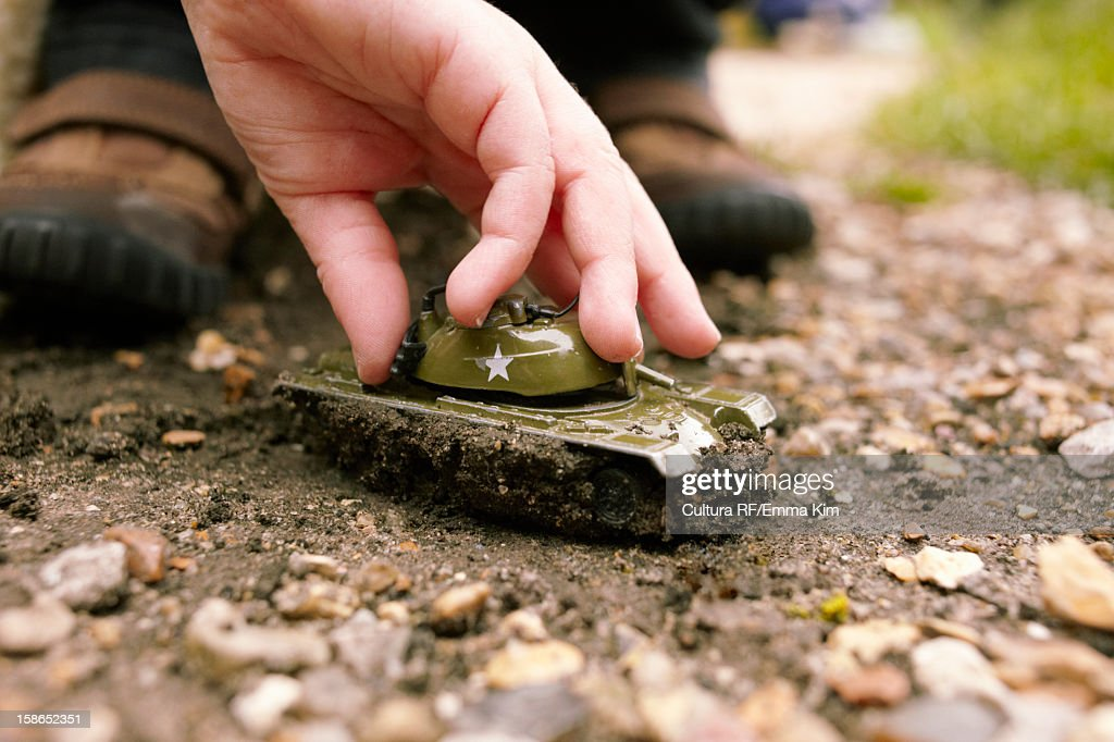 Boy playing with toy tank in dirt : Stock Photo