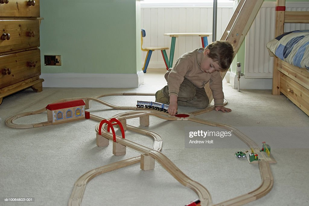 Boy (4-5) playing with toy train in room