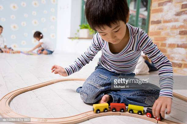 Boy (4-5 years) playing with toy train set, two girls (4-5 years) sitting in background, elevated view