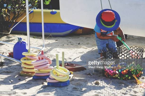 Boy Playing With Toys On Shore At Beach
