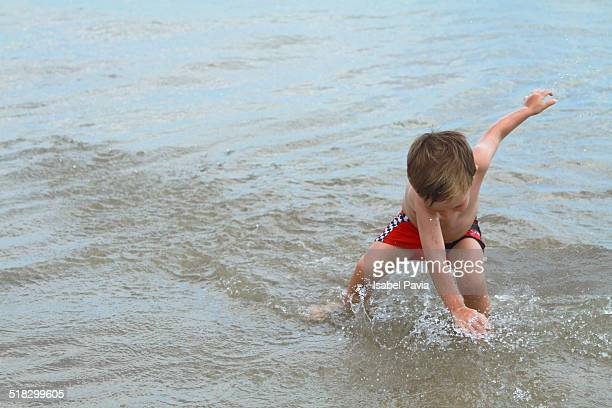 Boy playing with waves at beach