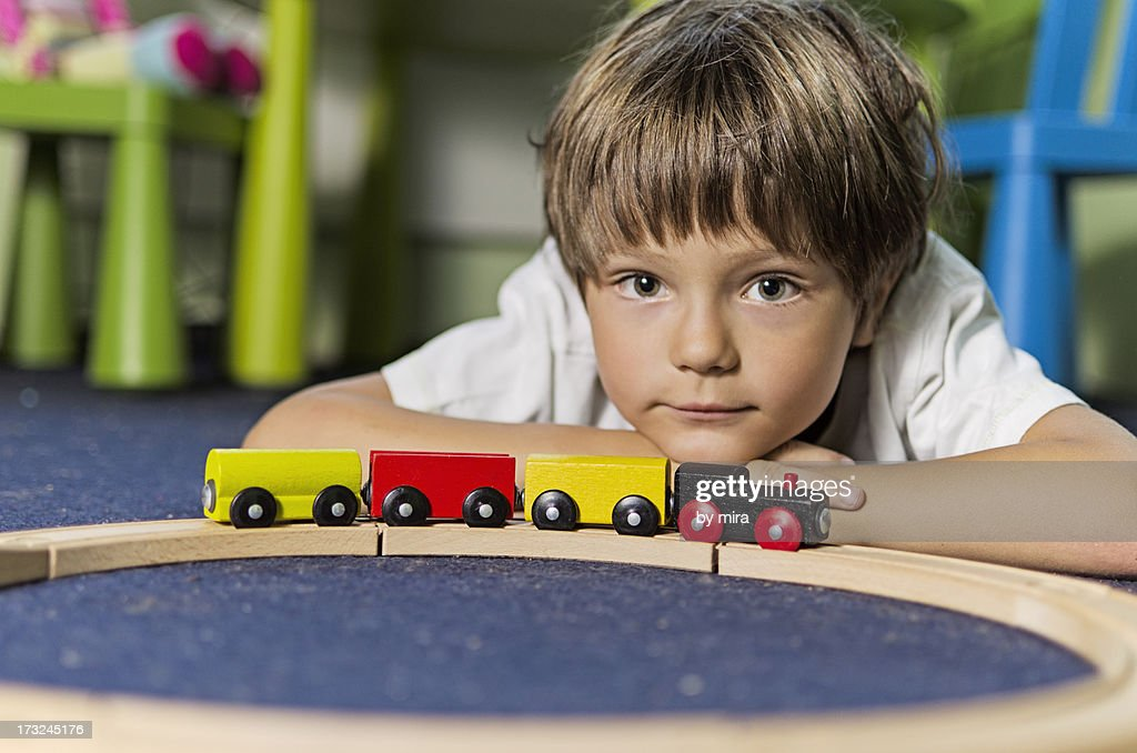 Boy playing with wooden toy train