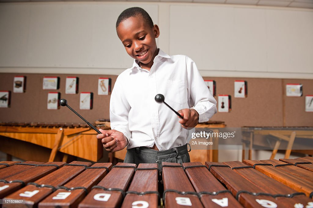 Boy playing wooden xylophone in classroom, Johannesburg, Gauteng Province, South Africa