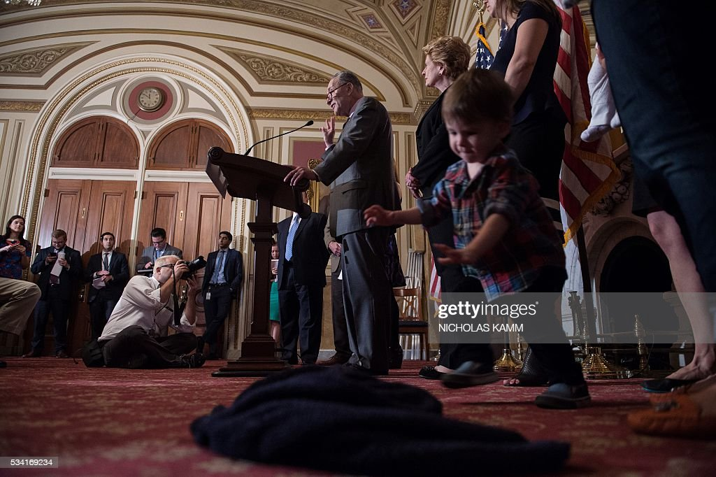 A boy plays as US Senator Charles Schumer (D-NY)holds a press conference with senators, health experts, and local mothers to demand that Congress pass emergency funding to combat the spread of the Zika virus in the US on Capitol Hill in Washington, DC, on May 25, 2016. / AFP / Nicholas Kamm