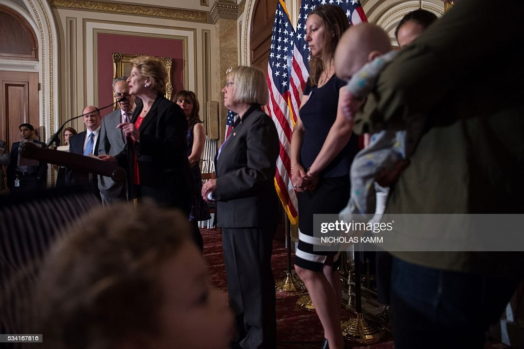 A boy plays as US Senator Debbie Stabenow holds a press conference with senators, health experts, and local mothers to demand that Congress pass emergency funding to combat the spread of the Zika virus in the US on Capitol Hill in Washington, DC, on May 25, 2016. / AFP / Nicholas Kamm