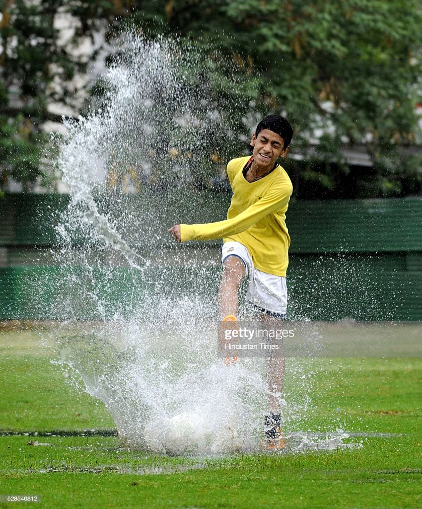 A boy plays football on a sunny cloudy day at a field in the morning, on May 5, 2016 in Noida, India. The national capital sizzling today as heat wave-like conditions prevailed across the city with mercury hovering above 40 degree Celsius, making life tough for the Delhiites.