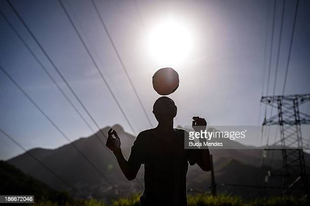 A boy plays football in the Formiga favela or shantytown on November 2 2013 in Rio de Janeiro Brazil The favela was previously controlled by drug...
