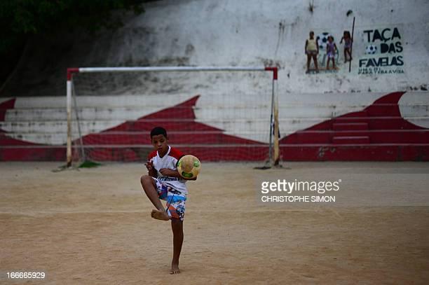A boy plays football on a field in the Cidade de Deus shantytown Rio de Janeiro Brazil on April 13 2013 AFP PHOTO/CHRISTOPHE SIMON