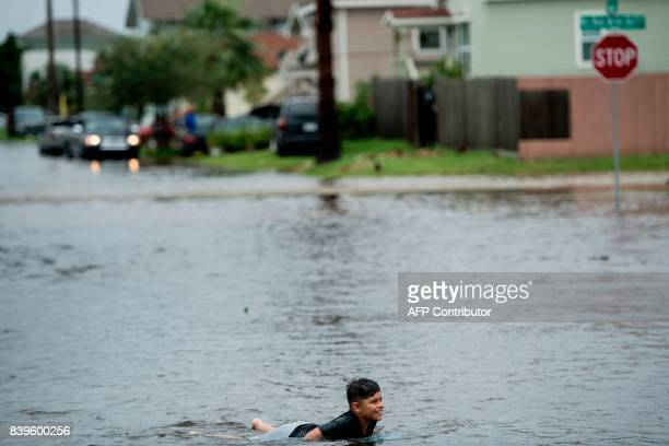 A boy plays in a flooded street as the effects of Hurricane Harvey are seen August 26 2017 in Galveston Texas Hurricane Harvey left a trail of...