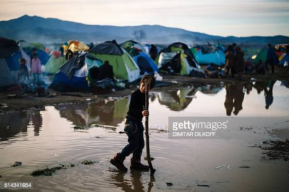 A boy plays in a mud puddle at a makeshift camp of the GreekMacedonian border near the Greek village of Idomeni on March 8 where thousands of...