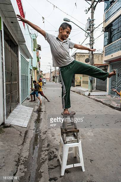A boy plays in a paved street in Uniao de Vila Nova recently converted in the framework of a favela upgrading project by the Sao Paulo state housing...
