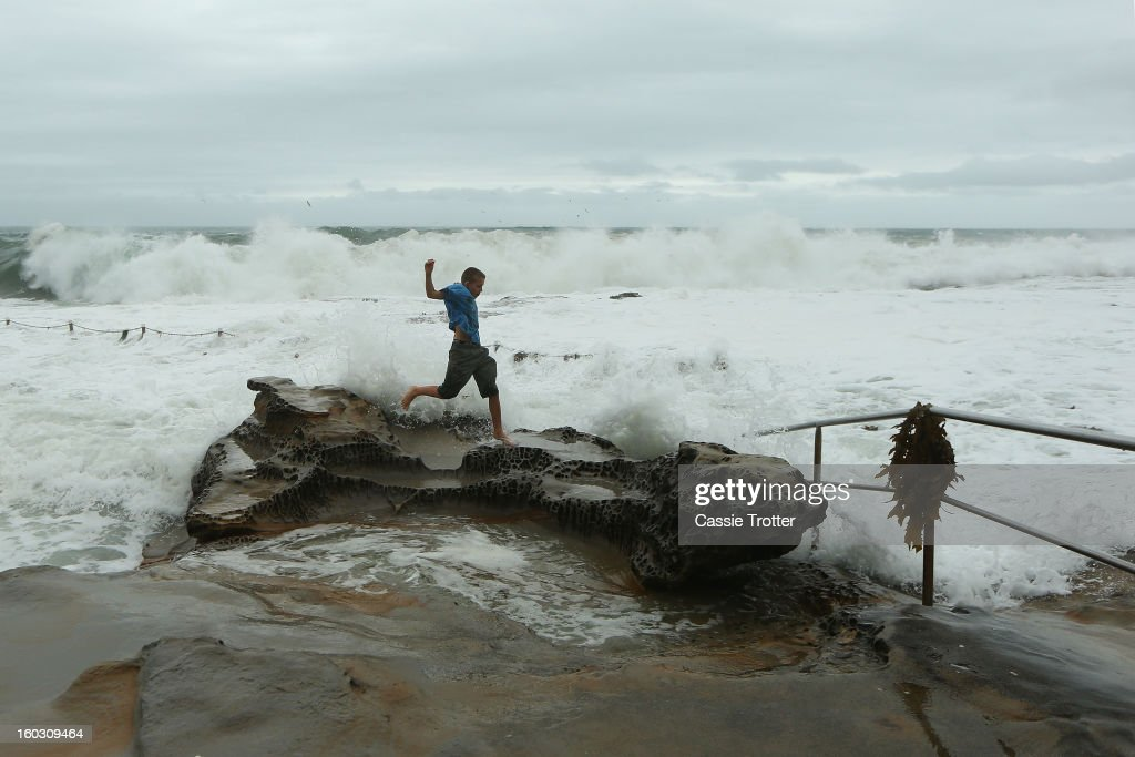 A boy plays in the large swell at the Dee Why baths after a storm overnight hit Sydney on January 29, 2013 in Sydney, Australia. Parts of Sydney are experienced record rainfall after ex-cyclone Oswald swept through the city last night.