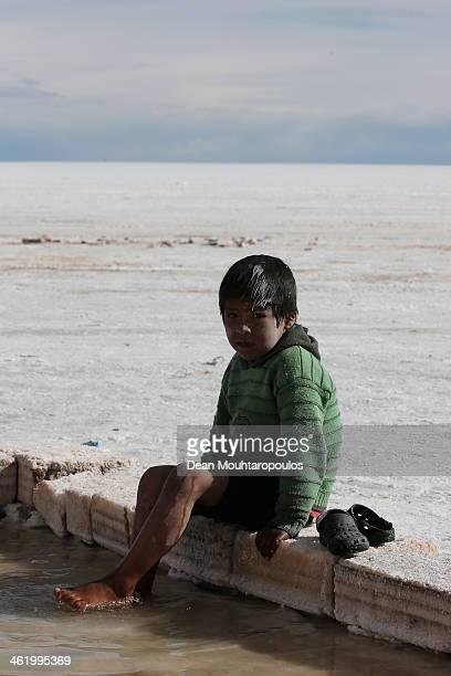 A boy plays in the salt water at the Salar de Uyuni or Uyuni Salt Flat during Day 7 of the 2014 Dakar Rally on January 11 2014 in Uyuni Bolivia