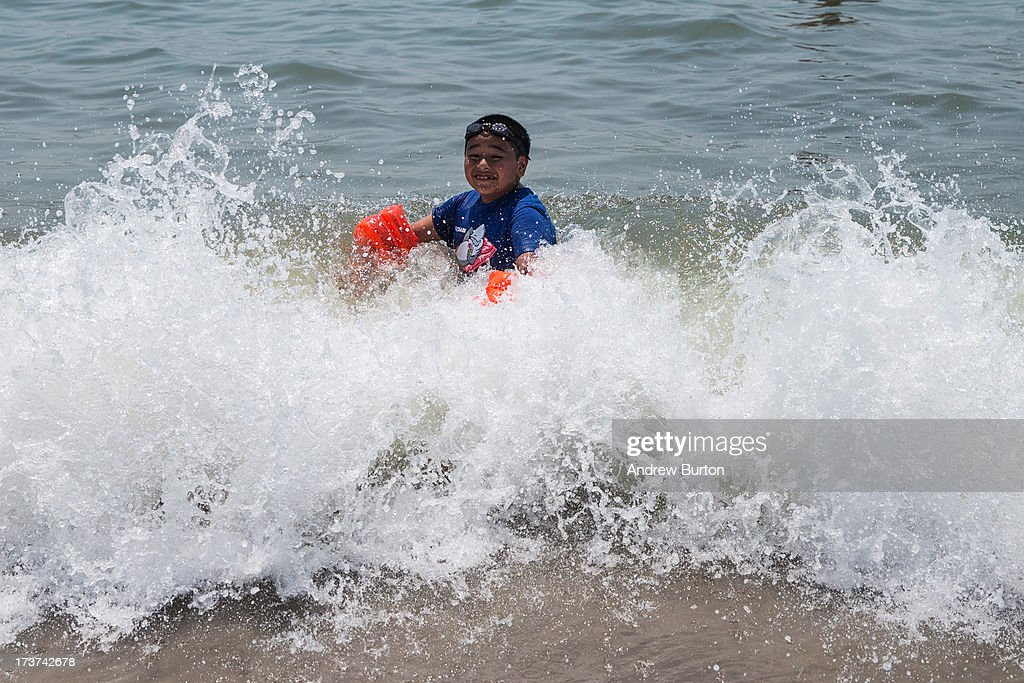 A boy plays in the waves at Rockaway Beach during a heat wave on July 17 2013 in the Rockaway Beach neighborhood of the Queens borough of New York...