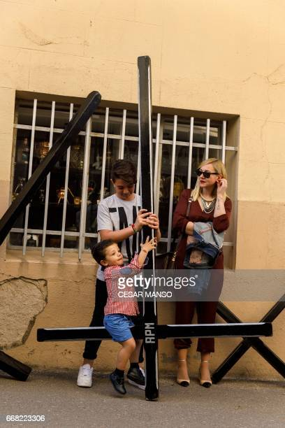 A boy plays on a cross before the Ecce Homo Passion procession during Holy Week in the northwestern Spanish village of Fuentesauco on April 13 2017...