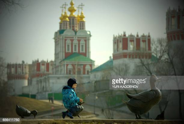 TOPSHOT A boy plays on a sculpture of a duck and ducklings with Moscow's Novodevichy Convent seen in the background on March 22 2017 / AFP PHOTO /...