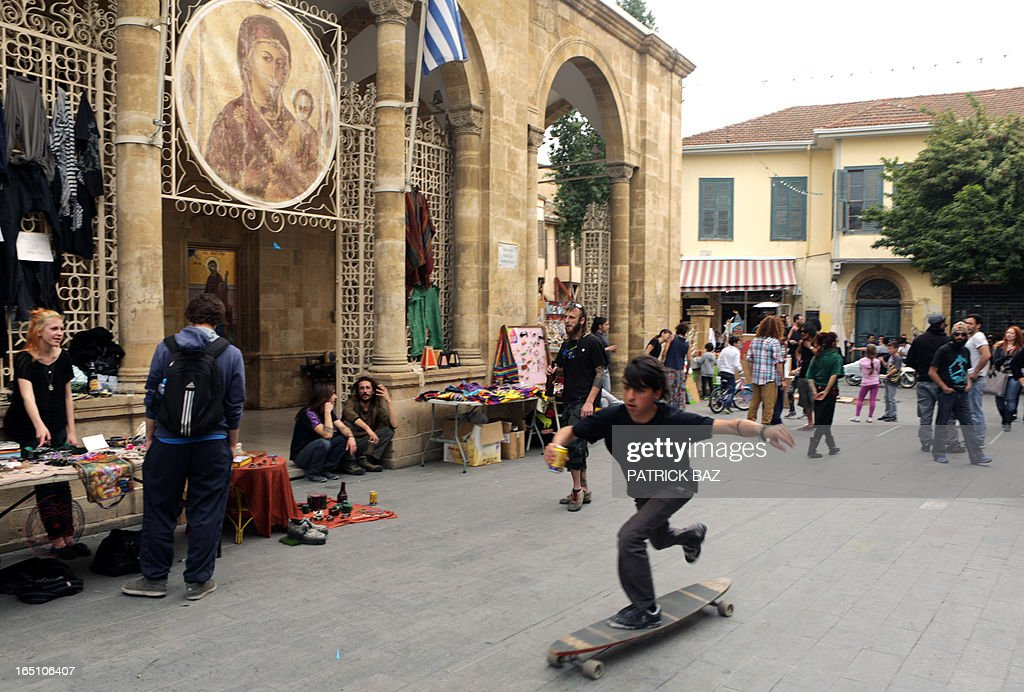 A boy plays on a skateboard past street vendors, at a makeshift market in the old part of Nicosia on March 30, 2013. Big savers in Cyprus's largest bank face losses of up to 60 percent, far greater than originally feared under the island's controversial EU-led bailout plan, officials said on March 30. At left is the Faneromeni Church.