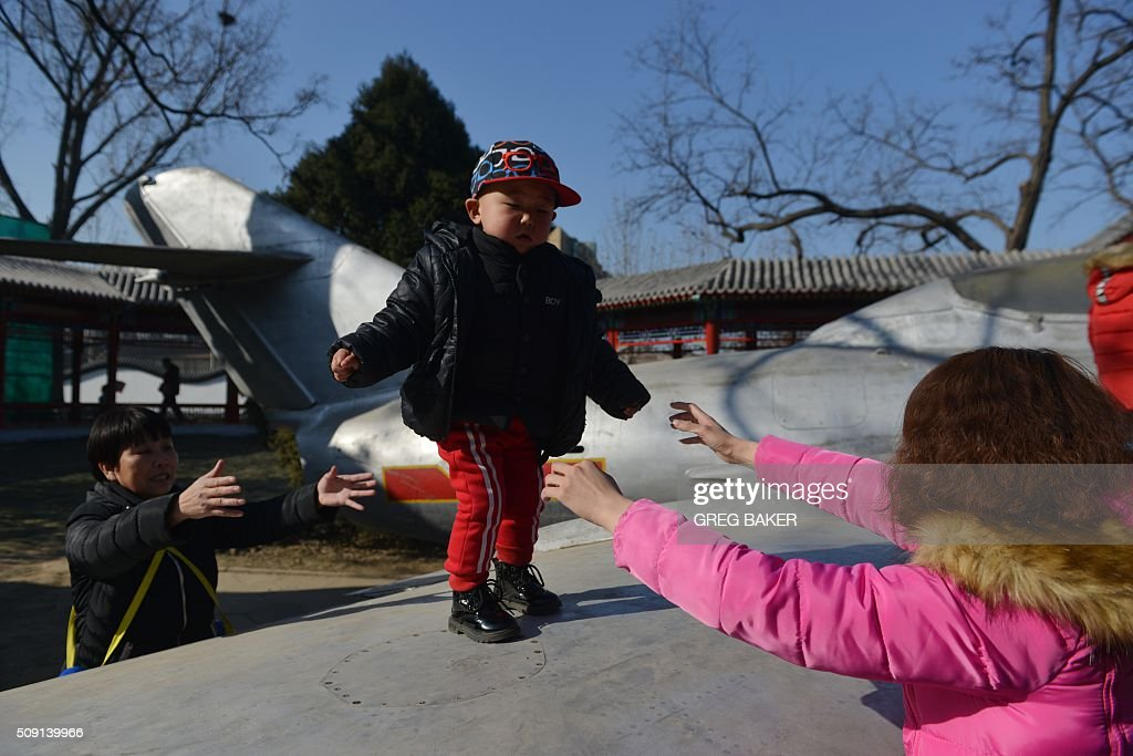A boy plays on the wing of an old Chinese fighter jet in a park in Beijing during Lunar New Year celebrations on February 9, 2016. Millions of Chinese are celebrating Spring Festival, the most important holiday on the Chinese calendar, which this year marks the beginning of the Year of the Monkey. AFP PHOTO / GREG BAKER / AFP / GREG BAKER