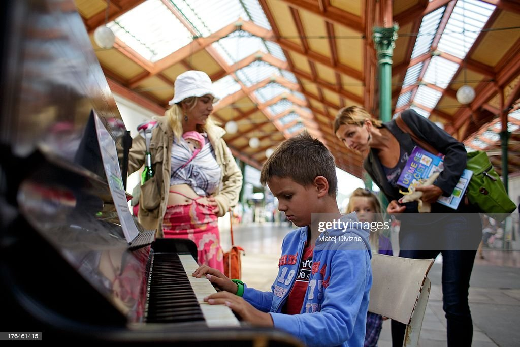 A boy plays piano during the first day of the 'Pianos on the street' project at Masaryk railway station on August 13, 2013 in Prague, Czech Republic. The project, by Prague cafe owner Ondrej Kobza, started in Prague today. Kobza placed pianos in five spots in the city centre for random passers-by to play. Similar projects run worldwide.