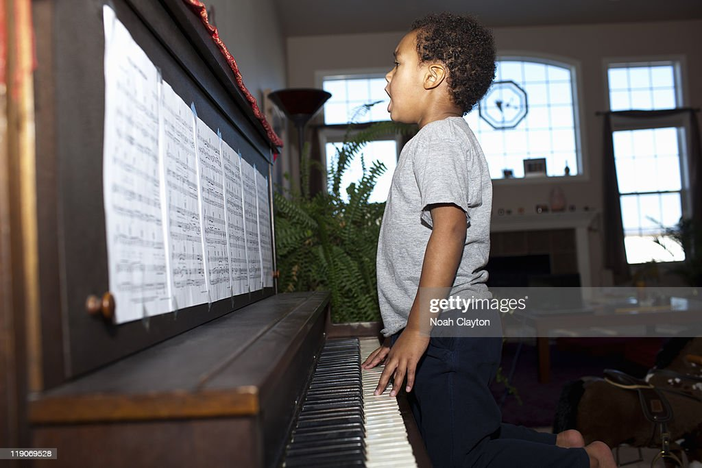 Boy plays piano in home : Stock Photo