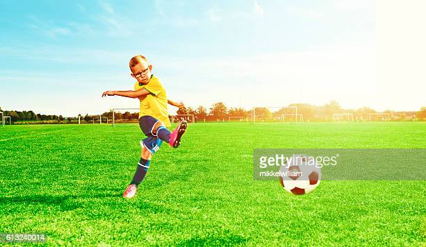 Boy plays soccer and kicks a ball on playing field