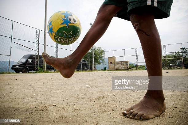A boy plays soccer in a sports court uphill as a vehicle of the Special Police Operations Battalion is seen on the background at the Morro dos...