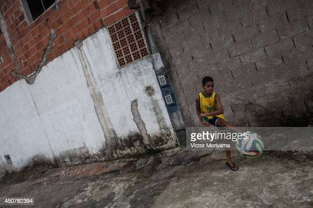 A boy plays soccer in the streets of the Garden Gloria neighborhood on June 17 2014 in Praia Grande Brazil Soccer star Neymar of Brazil lived in this...