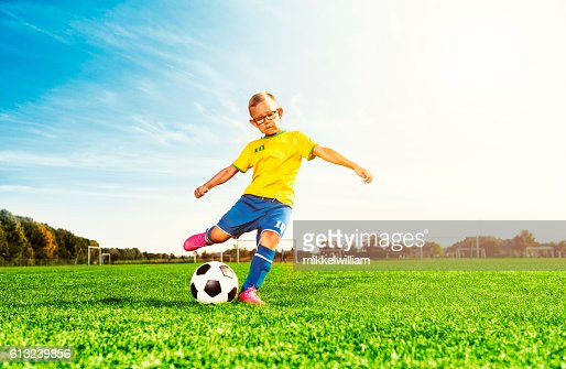 Boy plays soccer on field and kicks football