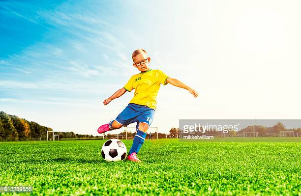 Boy plays soccer on field and kicks football