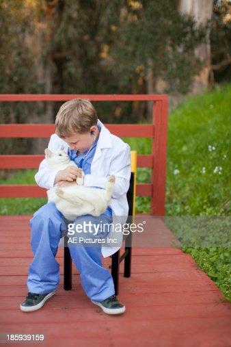 Boy plays veterinarian : Stock Photo