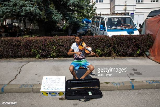A boy plays violin on the street in the town centre during the Guca Trumpet Festival on August 10 2017 in Guca Serbia Thousands of revellers attend...