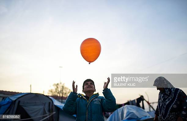 TOPSHOT A boy plays with a balloon next to a woman at the makeshift camp of the GreekMacedonian border near the Greek village of Idomeni on April 5...