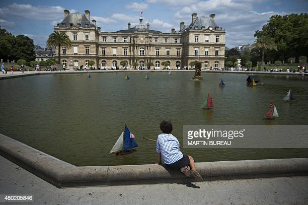 A boy plays with a boat at the Luxembourg gardens in Paris on July 9 2015 in Paris AFP PHOTO / MARTIN BUREAU