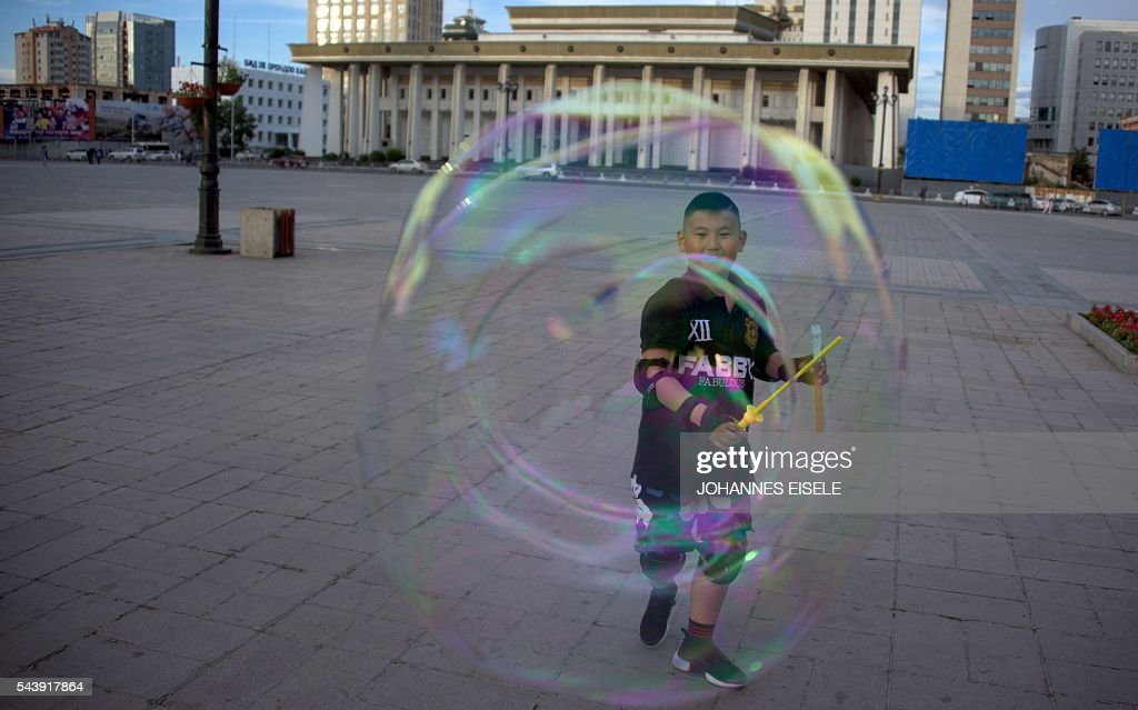 A boy plays with a bubble on the main square next to the Mongolian Parliament House in Ulan Bator on July 1, 2016. A landslide election victory by Mongolia's opposition is a stinging rejection of the government's failed economic policies, analysts and voters said, as the country struggles to turn its vast natural resources into national wealth. / AFP / JOHANNES