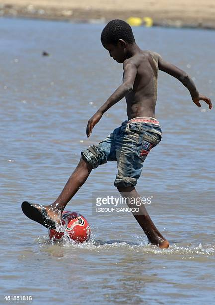 A boy plays with a football in a flooded street in the Adjoufou district of Abidjan on July 8 following a month of heavy rainfalls over the country's...